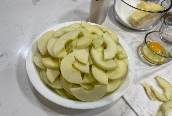 Place the sliced apples in pie pan