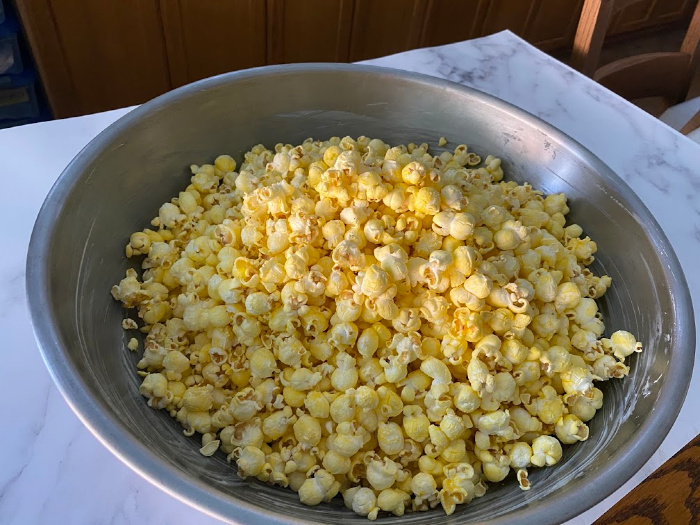 Place popped popcorn in buttered bowl