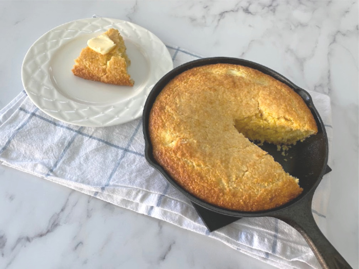 Cornbread cut and on a white plate