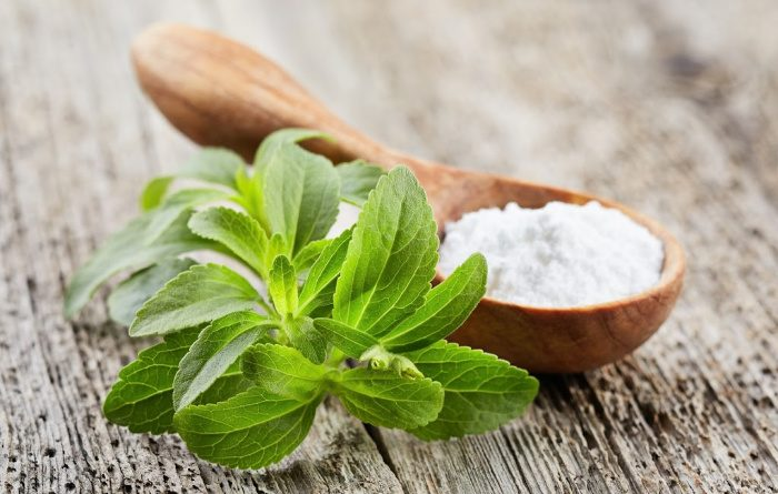 Stevia leaves and powder on wood plank